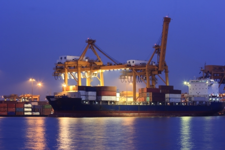 Industrial Container Cargo freight ship with working crane bridge in shipyard at dusk for Logistic Import Export background Archivio Fotografico