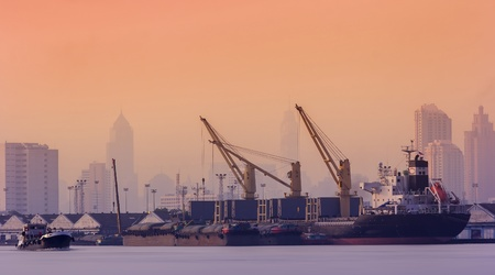 customs: Container Cargo freight ship with working crane bridge in shipyard at dusk for Logistic Import Export background