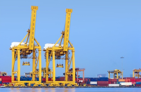 Container Cargo freight ship with working crane bridge in shipyard at evening for Logistic Import Export background