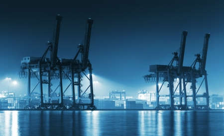 seaport: Container Cargo freight ship with working crane bridge in shipyard at dusk for Logistic Import Export background