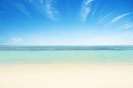Stranden, kristalhelder water, blauwe hemel als achtergrond. Stockfoto