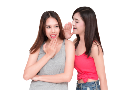 scandalous: Two women whispering and smiling.  isolated on white background.