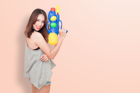 Girl holding a water gun and happy playing (for Songkran festival  day in Thailand).