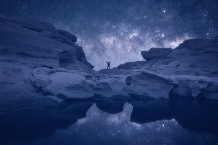 starry night: Night landscape with Milky Way. Silhouette of a standing young man with raised up arms on the mountain. Beautiful Universe. Travel background with blue night starry sky