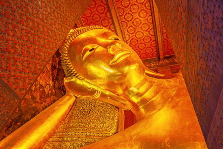 Beautiful face of Reclining Buddha,and thai art architecture in Wat Phra Chetupon Vimolmangklararm (Wat Pho) temple in Thailand.