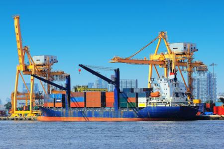 Containervrachtvrachtschip met werkende kraanbrug in scheepswerf.