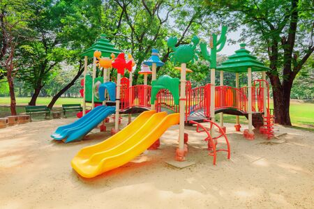 Colorful children playground activities in public park surrounded by green trees