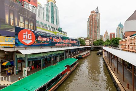 Bangkok - Thailand, 3 Aug 2019: Pratunam pier, express boat public transport stop in center of city. Saen Saep canal. Busy traffic on Ratchadamri road