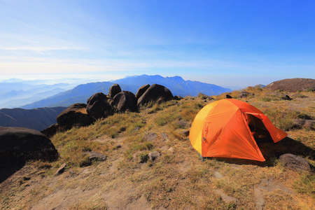 Orange tent on a high hill in the morning