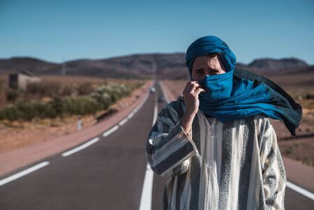Arab person with blue bereber turban in middle of a road near desert Фото со стока
