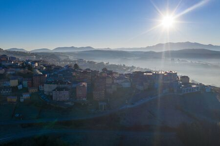 Aerial shot of a town in northern spain with fog and sun 版權商用圖片