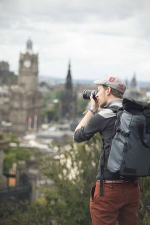 Photographer with backpack and a hat shooting buildings of Edinburgh in a sunny day