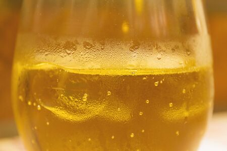 old cider drink with ice in glass close up
