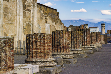 columns and ruins of ancient city of Pompeii in Italy with mountains in the background