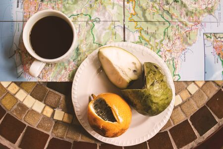 anona: exotic tropical fruits with coffee and Madeira maps on table top view, energy break