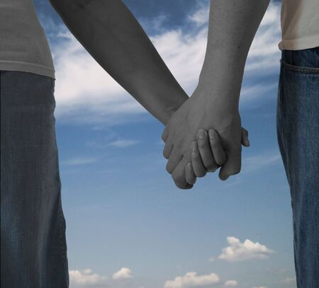 Couple Holding hands - black and white combined with color on sky background