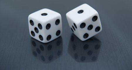 two (2) white dice on black reflective background - snake eyes