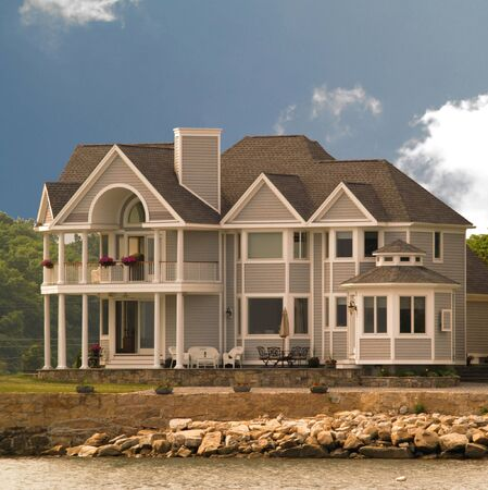 suburbia: Large House build on beach of ocean or lake  Stock Photo