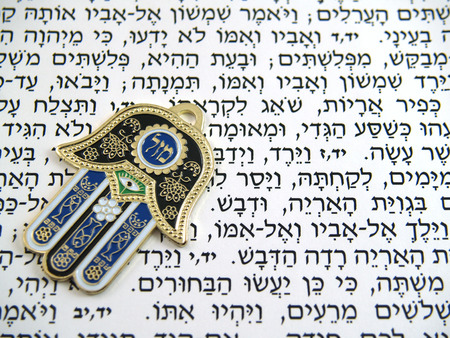 Hamsa kabbalah good luck charm on Hebrew bible Banco de Imagens - 1606170