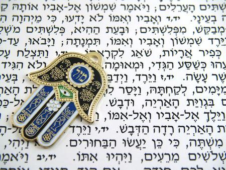 kabbalah: Hamsa kabbalah good luck charm on Hebrew bible Stock Photo