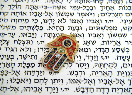 judaica: Hamsa kabbalah good luck charm on Hebrew bible Stock Photo