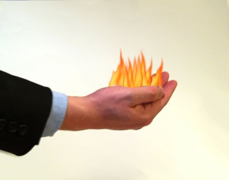 Businessman holding fire in the palm of his hand