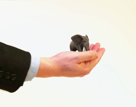 Businessman holding a miniature elephant in the palm of his hand.