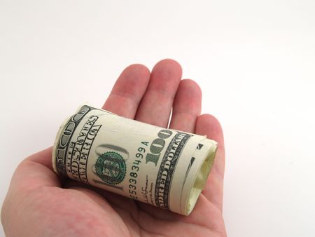 Roll of one hundred dollar bills held out in hand