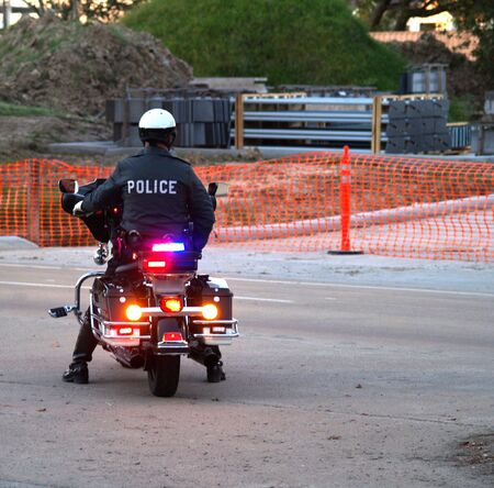 Police officer sitting on Motorcycle  - back view photo