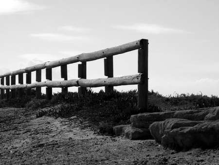 Old wooden log fence with sky background - bw Stock Photo