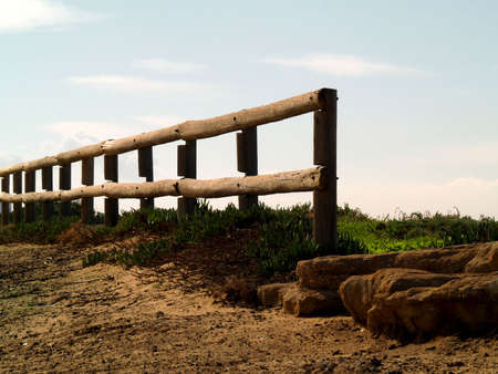 Old wooden log fence with sky background