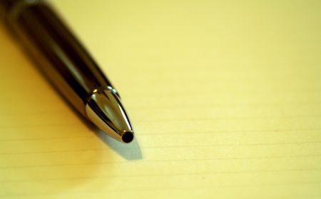 Close up Tip of elegant pen on an open notebook