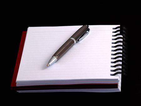 pen on notebook on black photo