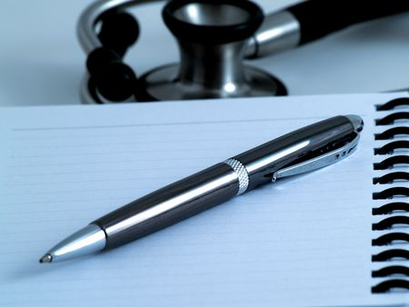 Note pad with pen on it and stethoscope in background -night Stock Photo