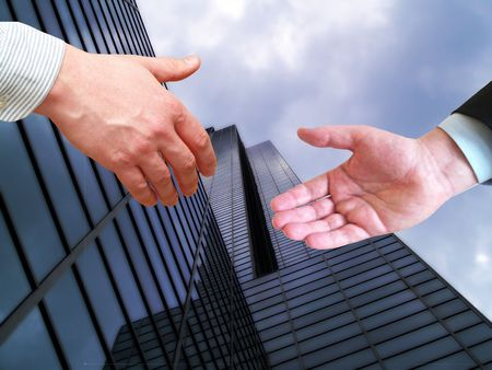 two businessmen shaking hands on tall Corporate office building background Stock Photo