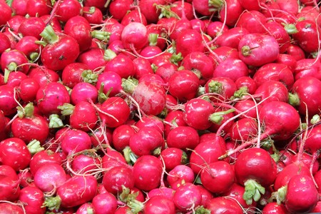 Photo of a pile of red radishes in an open market