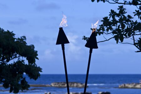 torches lit at dusk in front of ocean