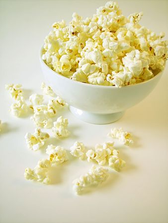 Buttered popcorn in white bowl, on white background.