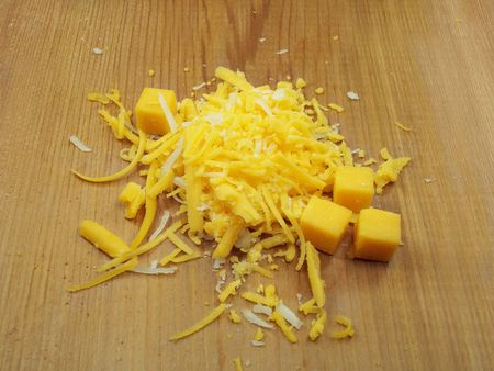 Grated Cheese on cedar board. Standard-Bild