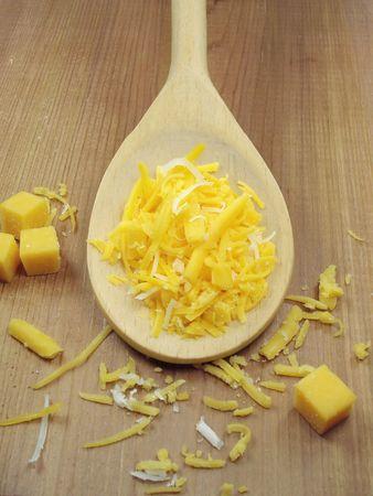 Geraspte kaas op een houten lepel. Stockfoto - 248974