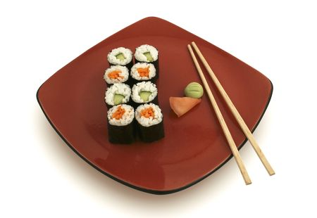 Sushi rolls on red plate with ginger and wasabi.