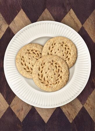 oatmeal: Three oatmeal cookies on white plate, on diamond placemat