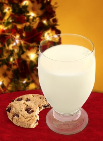 Chocolate Chip Cookie with bite taken and a glass of Milk on a Christmas background.  photo