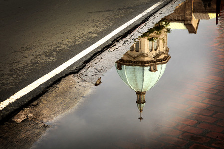 An old church tower reflected in a puddle of rainwater.