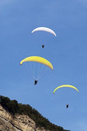 descending: Three paragliders descending along a mountainside