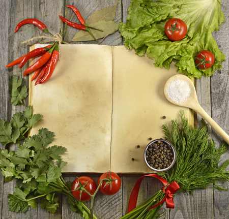 Open cook book with vegetables and products on wooden table background