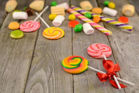 Lollipops with sweet things on the wooden table photo
