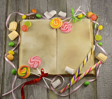 Open book with sweet goods on wooden table photo