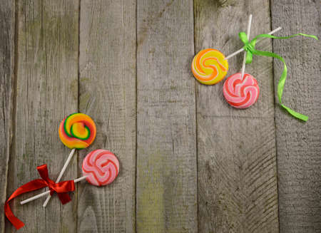 Border with lollipops on wooden background, with copy space photo