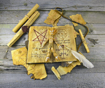 necromancy: Halloween still life of Necronomicon book with straw voodoo doll and parchments